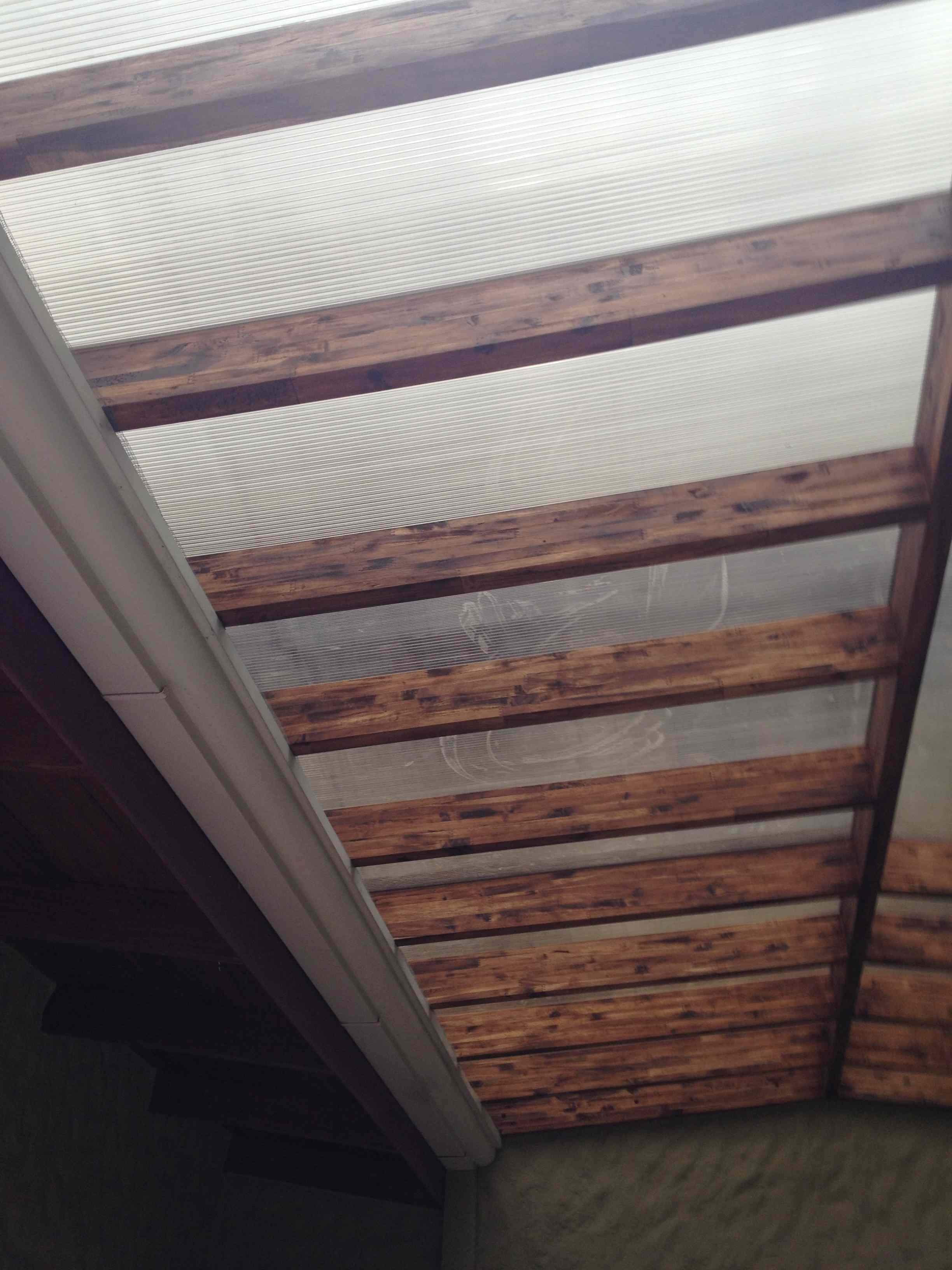 Close up of laminated acacia rafters and plastic roof covering